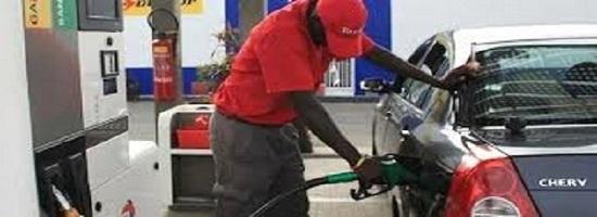 Un gerant de station service en train de servir du carburant